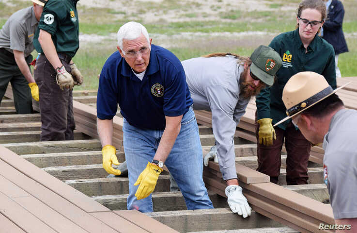 U.S. Vice President Mike Pence helps National Park Service workers lay planks along a boardwalk near Old Faithful Geyser in Yellowstone National Park in Wyoming, June 13, 2019.