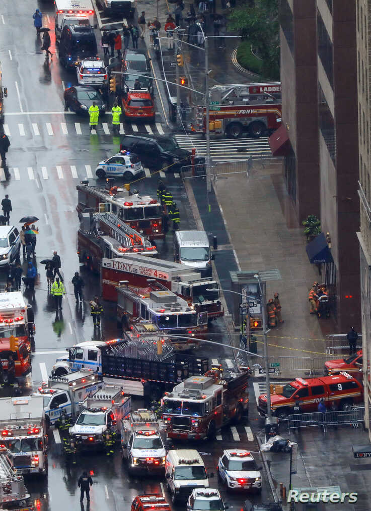 Emergency vehicles are seen outside 787 7th Avenue in midtown Manhattan where a helicopter crashed in New York