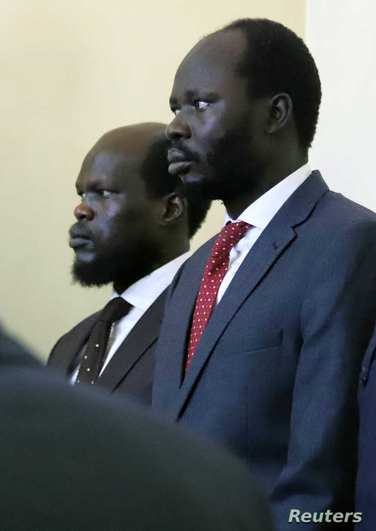 Kerbino Wol, a businessman, and Peter Biar Ajak, the South Sudan country director for the London School of Economics International Growth Centre based in Britain, stand in the dock inside the courtroom in Juba