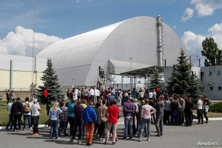 Visitors stand outside the New Safe Confinement (NSC) structure over the old sarcophagus covering the damaged fourth reactor at the Chernobyl Nuclear Power Plant, in Chernobyl.