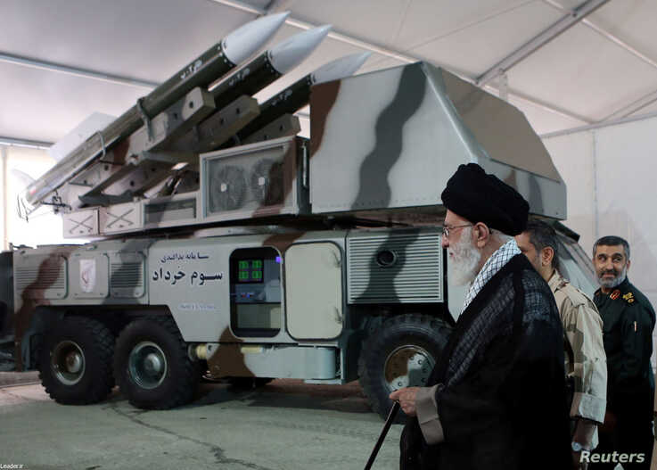 """FILE - Iran's Supreme Leader Ayatollah Ali Khamenei is seen near a """"3 Khordad"""" system which is said to had been used to shoot down a U.S. military drone."""