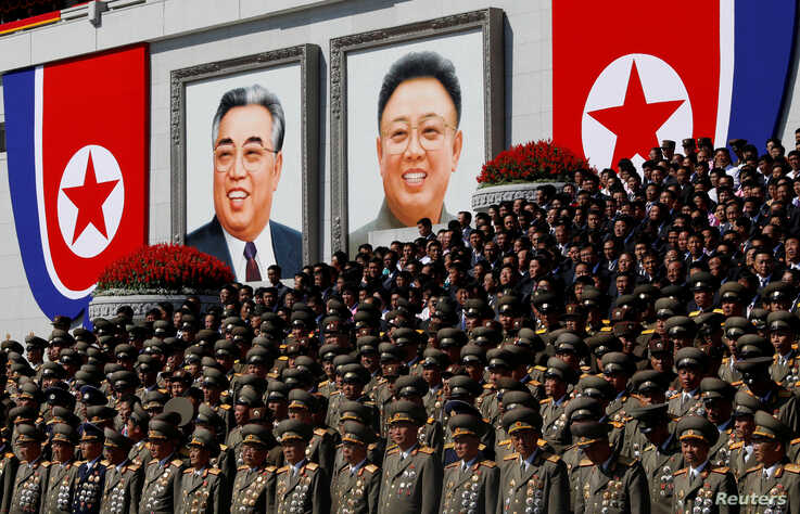 FILE PHOTO: Senior military officials watch a parade as portraits of late North Korean leaders Kim Il Sung and Kim Jong Il are seen at the main Kim Il Sung square in Pyongyang