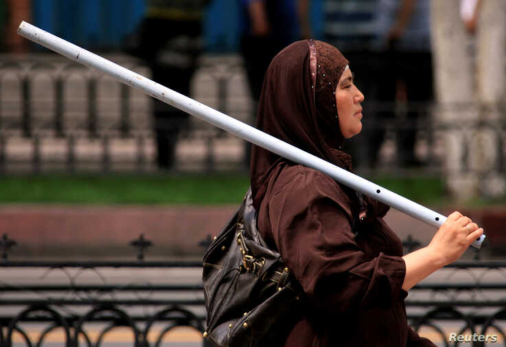 FILE PHOTO: An ethnic Uighur woman carries a metal rod as she walks down a main road in the city of Urumqi in China's Xinjiang Autonomous Region