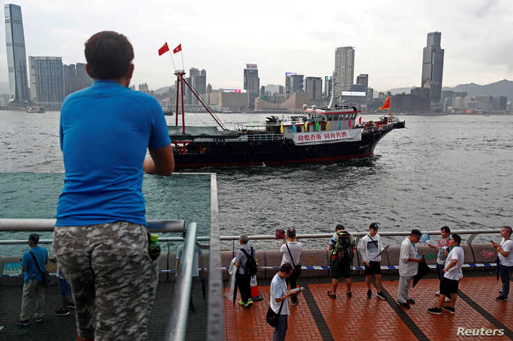 """A vessel displaying a banner saying """"Cherish Hong Kong, Stay Together"""" passes Victoria Harbour during a pro-government rally in Hong Kong"""