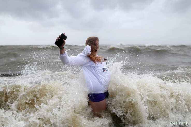 Audrey Ulfers stands on the shore of Lake Pontchartrain during Hurricane Barry in Mandeville, La., July 13, 2019.