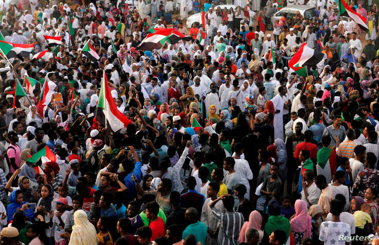 FILE PHOTO: Sudanese people celebrate on the streets of Khartoum