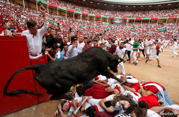 A wild cow jumps over revelers after the last bull run of the San Fermin festival in Pamplona, Spain, July 14, 2019.