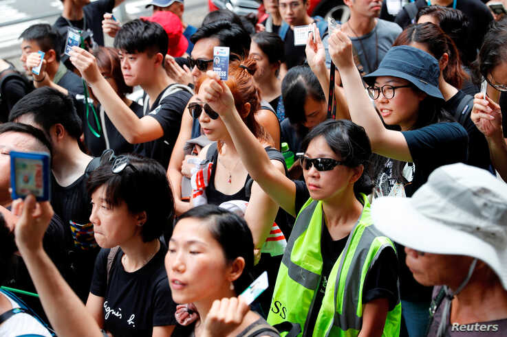 Journalists hold up their press cards as they stage a silent march to Police Headquarters to denounce media treatment during protest against a proposed extradition bill, in Hong Kong, July 14, 2019.