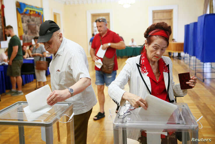 Voters cast their ballots at a polling station during Ukraine's parliamentary election in Kiev