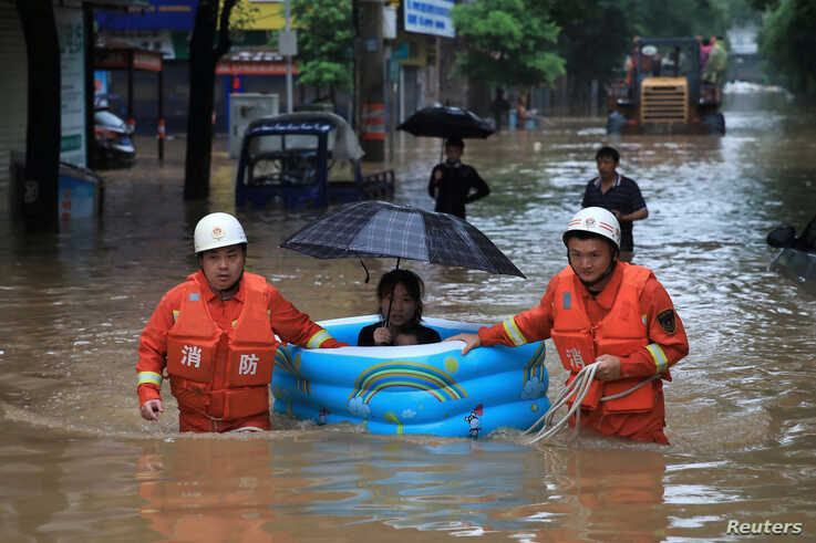 Rescue workers wade through flood waters as they evacuate a woman with an inflatable swimming pool following heavy rainfall in Pingxiang, Jiangxi province, China, July 9, 2019.