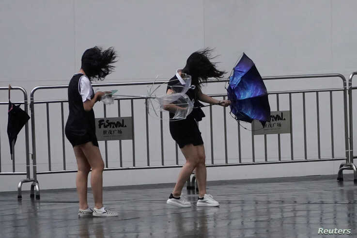 People walk in the rainstorm as Typhoon Lekima approaches Shanghai, China, Aug. 10, 2019.