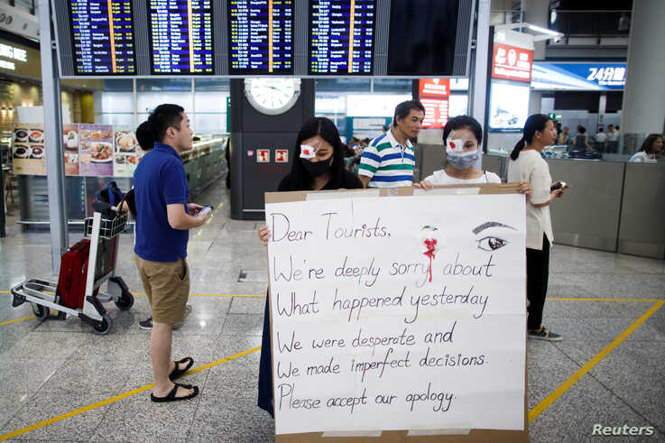 Anti-government demonstrators apologize for yesterday's clashes with police at the airport in Hong Kong, Aug. 14, 2019.