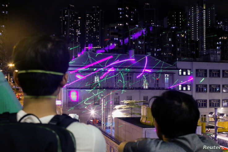 Anti-extradition bill protesters watch as demonstrators point laser pens at the police station in Sham Shui Po in Hong Kong, China, August 14, 2019.  REUTERS/Thomas Peter