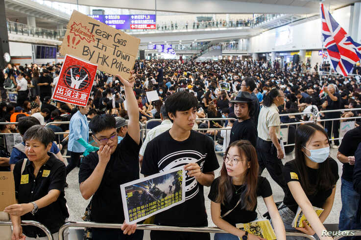 Anti-extradition bill protesters hold up placards for arriving travellers during a protest at the arrival hall of Hong Kong International Airport in Hong Kong, China August 9, 2019.  REUTERS/Thomas Peter