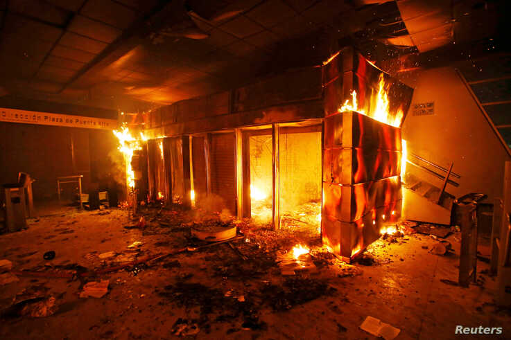A subway ticket office is seen on fire during a protest against the increase in the subway ticket prices in Santiago, Chile,…