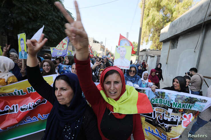 Kurdish and Arab protesters chant slogans against Turkish President Tayip Erdogan as they walk during a march to the United…