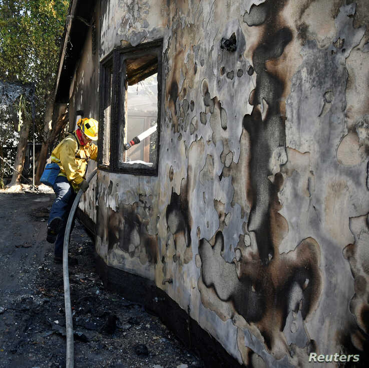 A firefighter douses water on a house after it was burned by the wind-driven Getty Fire in West Los Angeles, California, U.S…