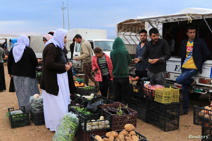 Displaced people from the Yazidi religious minority buy vegetables at the Sharya camp, in Duhok, Iraq October 29, 2019. Picture…