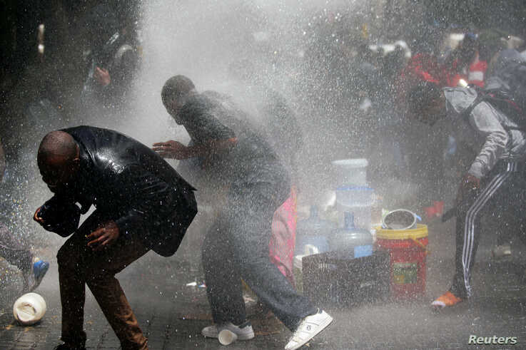 Police fire a water cannon at refugees evicted from a sit in protest against xenophobia outside the United Nations High…