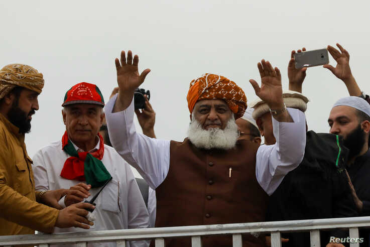 Fazal-ur Rehman, President of the Jamiat Ulema-e-Islam-Fazal (JUI-F) waves to supporters during what participants call Azadi…