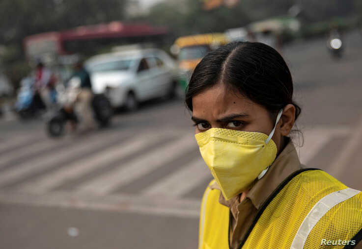 A policewoman wears a mask to protect herself from air pollution at a junction during restrictions on private vehicles based on…