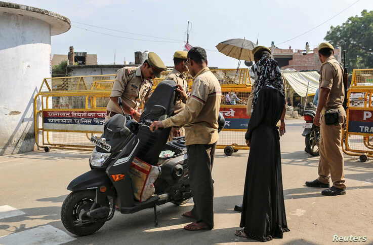 Policemen check a scooter at a security barricade on the road leading to a disputed religious site where Hindu religious groups…