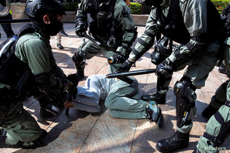 Riot police officers use pepper spray as they detain a protester during a demonstration at the Central District in Hong Kong,…