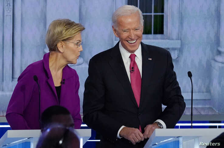 Democratic presidential candidate and Senator Elizabeth Warren talks with former Vice President Joe Biden during a break at the…