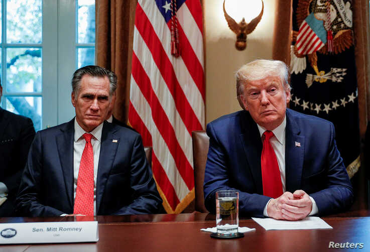 U.S. President Donald Trump listens to U.S. Senator Mitt Romney (R-UT) during a listening session on the regulation of nicotine…