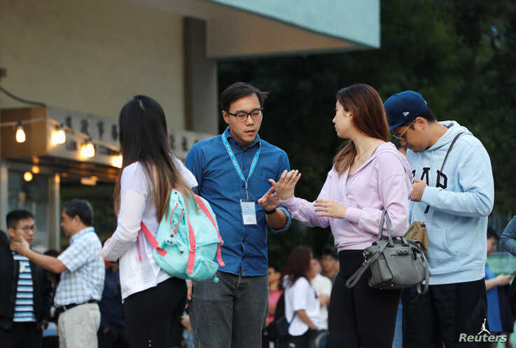 Electoral staff helps a voter at a polling station during district council local elections in Hong Kong, China November 24,…