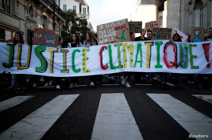 "Youth for Climate activists hold a banner which reads: ""climate justice"" as they demonstrate during a day of protest to…"