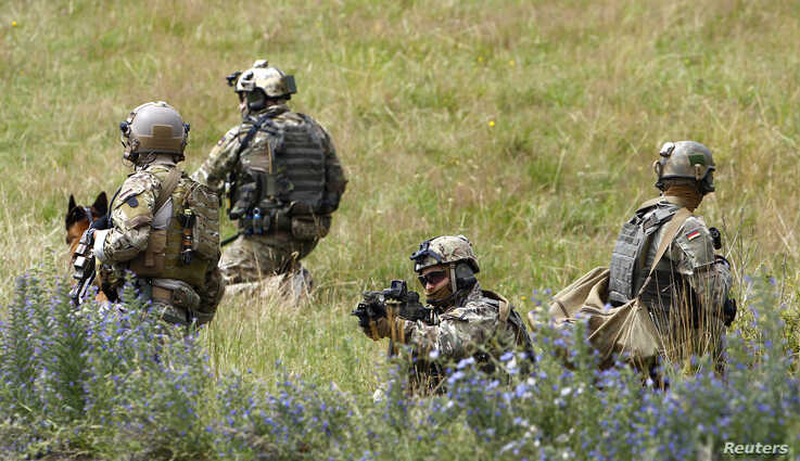 Members of German army Bundeswehr Special Forces Command (KSK) secure the area while demonstrating their skills at the Vehicle…