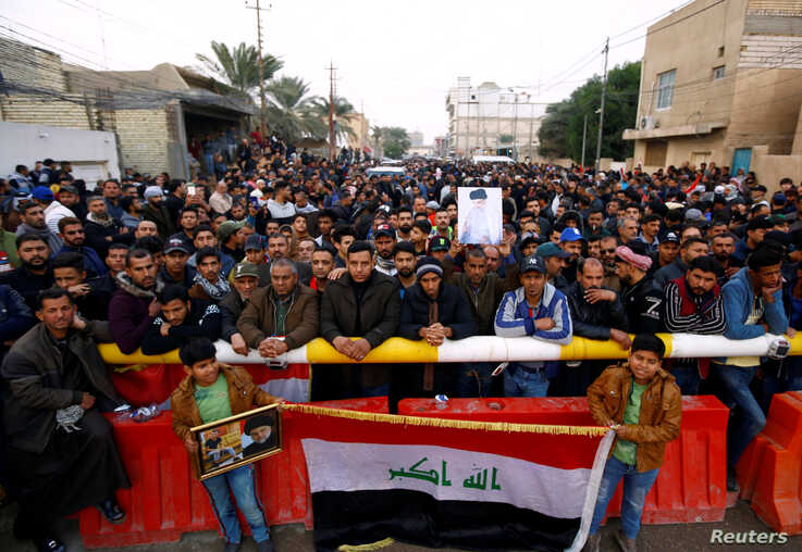 Supporters of Iraqi Shi'ite cleric Moqtada al-Sadr gather near his home, after it was attacked, in the holy city of Najaf, Iraq…