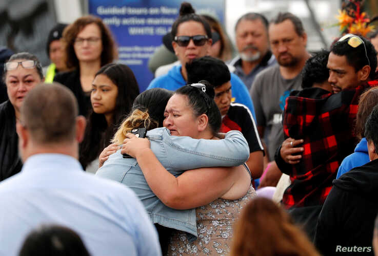 Relatives hug as they wait for rescue mission, following the White Island volcano eruption in Whakatane, New Zealand, December…