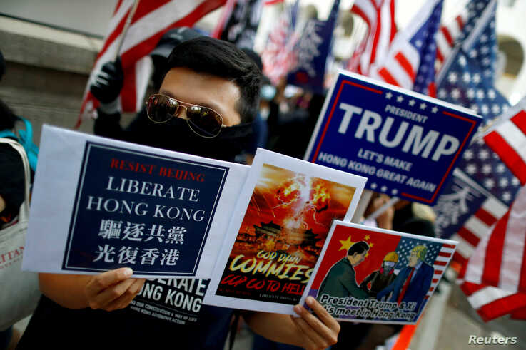 """A masked protester holds placards during a """"March of Gratitude to the US"""" event in Hong Kong, China December 1, 2019. REUTERS…"""
