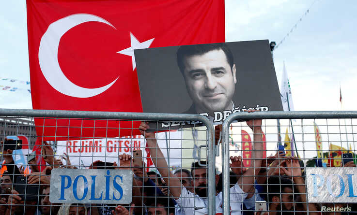 FILE PHOTO: A supporter of Turkey's main pro-Kurdish Peoples' Democratic Party (HDP) holds a portrait of their jailed former…