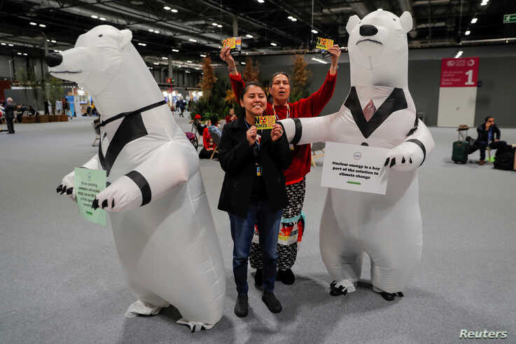 Anti-nuclear activists stand next to men dressed as polar bears holding banners advocating for nuclear energy as a solution for…
