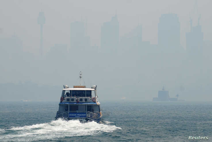 A ferry makes its way from Taronga Zoo to Circular Quay, with the CBD skyline barely visible in the background through smoke…
