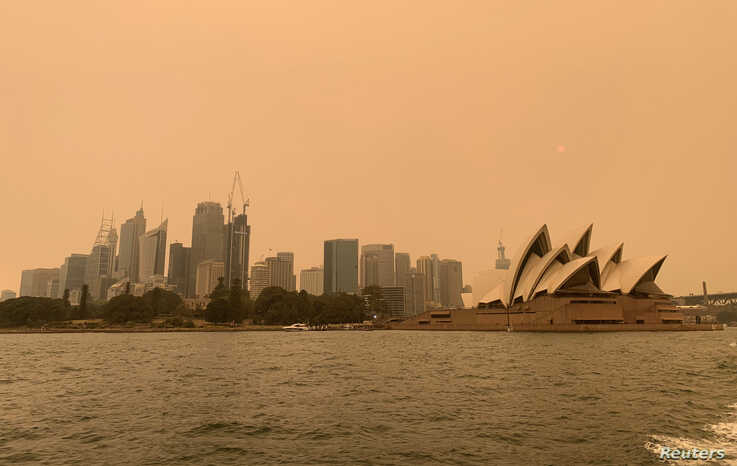 The haze from bushfires obscures the sun setting above the Sydney Opera House in Sydney, Australia, December 6, 2019. REUTERS…