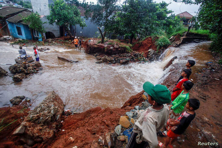 People look at a dam which collapsed after heavy rains in Bogor, West Java province, Indonesia January 2 2020, in this photo…