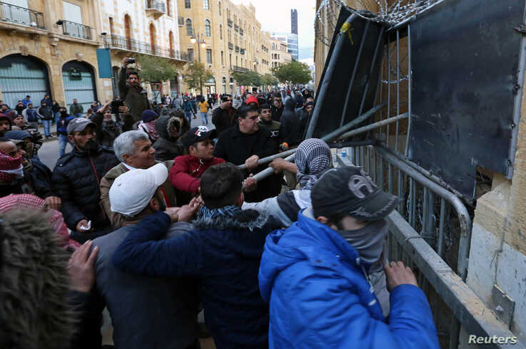 Demonstrators attempt to remove a barrier fence during a protest against the newly formed government in Beirut, Lebanon January…
