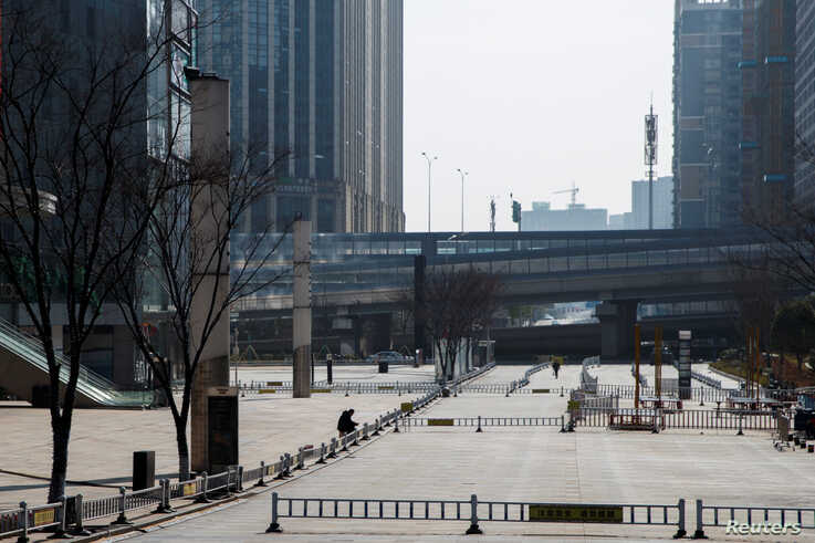 A man sits in a deserted shopping area in Changsha, Hunan province, China, as the country is hit by an outbreak of a new…