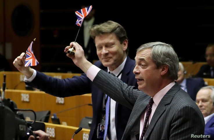 Brexit Party leader Nigel Farage along with other MEPs wave British flags ahead of a vote on the Withdrawal Agreement at the…