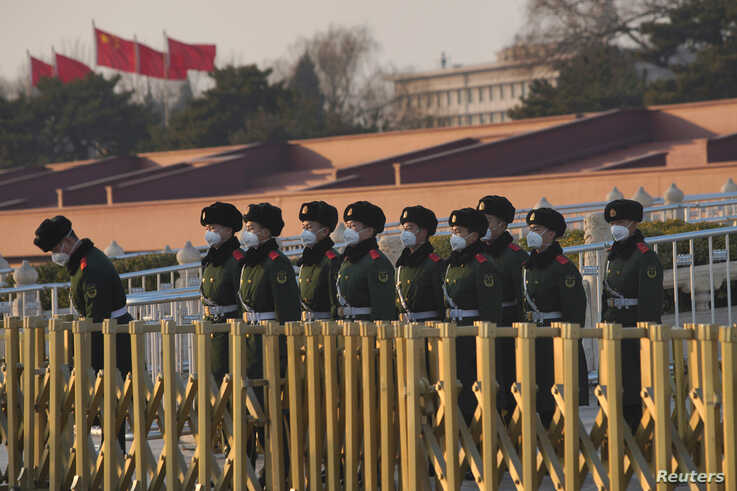 Paramilitary officers wearing masks line up in front of the Tiananmen Gate, as the country is hit by an epidemic of the new…