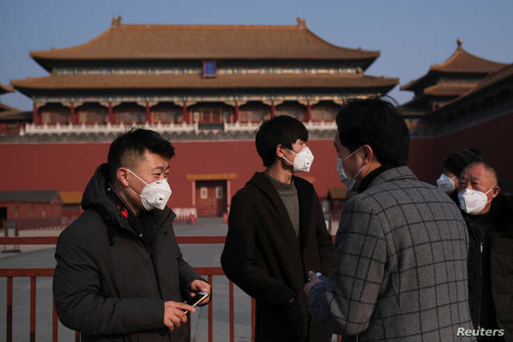 People wearing protective masks stand outside the main entrance of the Forbidden City where a notice is seen saying that the…