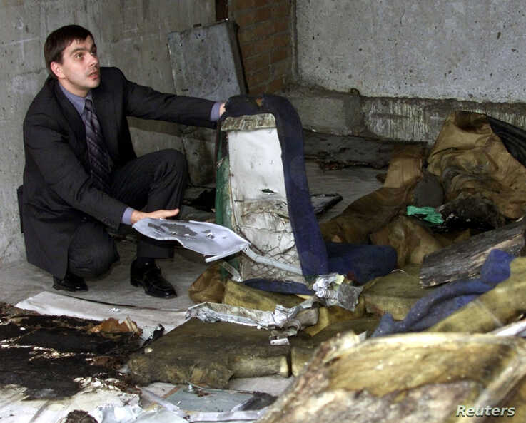 Viacheslav Filev, general director of Russia's Sibir airlines, shows a perforated seat of the crashed Tupolev TU-154 plane, in…