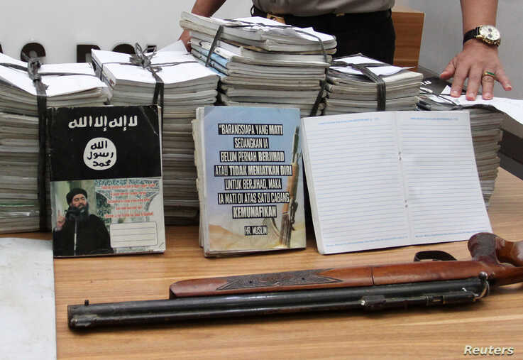 Indonesian police show scores of notebooks inscribed with Islamic State propaganda seized during a raid on the home of…