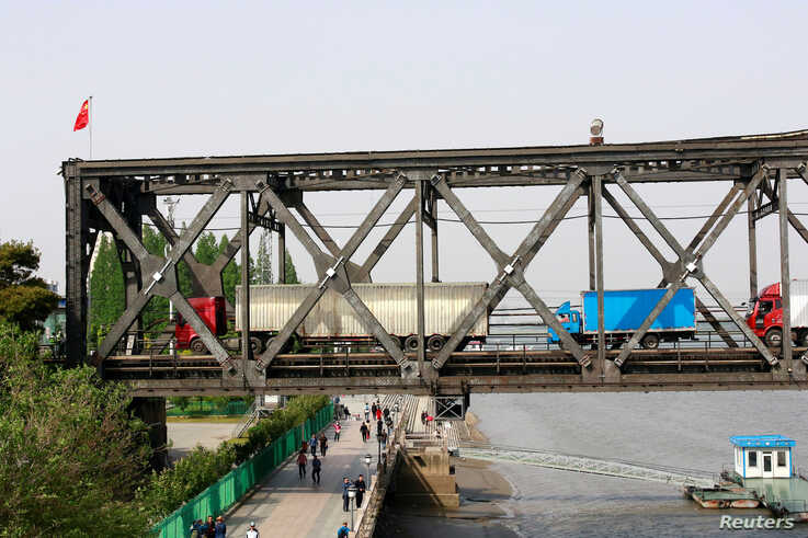 FILE PHOTO: Trucks wait for border inspection at the Chinese end of the Friendship Bridge that connects Sinuiju, North Korea…