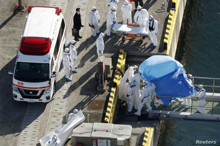 Officers in protective gear escort a person (under the blue sheet)  who was on board cruise ship Diamond Princess and was tested positive for coronavirus, in Yokohama, south of Tokyo in this photo taken by Kyodo, Feb. 4, 2020.