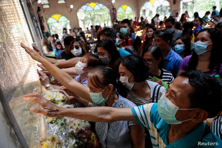 Filipino Catholics pray with protective masks on following confirmed cases of coronavirus in the country, at the National…
